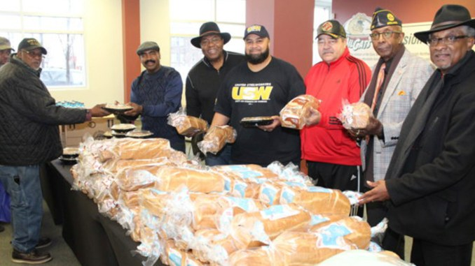 AFTER PICKING UP their hams, local veterans and their families selected desserts and the rest of the Christmas dinner trimmings as they moved through the serving line manned by Webb House volunteers including (l -r): Steve Mays, former Chicago Bear Jim Osborne, Machail Watkins, United Steelworkers Local 1014, Nate Cain, Robert Buggs and Indiana State Senator Lonnie Randolph.