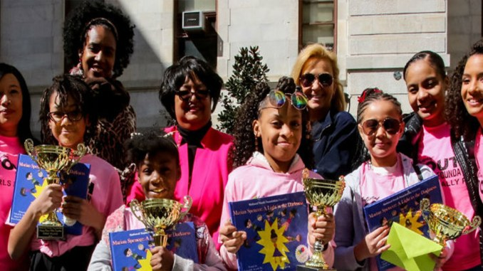"""In front, from left, are Winton Hill Academy students Serenity Mills, Aliyana O'Neal, Nakiyah Ray and Janyia New. In back, from left, are Sophia Hanson, National Youth Foundation co-founder; Nikki Maxwell, """"Dork Diaries"""" illustrator; Rachel Renee Russell, """"Dork Diaries"""" author; Julie Dellecave, Winton Hills Academy fourth-grade teacher; Jamee Joppy, NYF co-founder; and Carolyn Crawford, NYF co-founder. Photo provided"""
