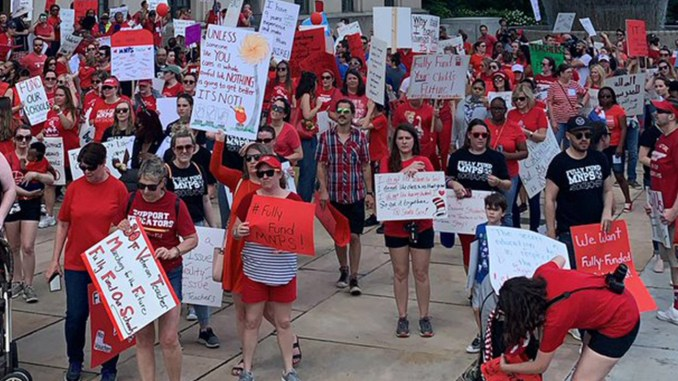 A sea of red t-shirts descends upon the Metro Courthouse in support of a 10% raise for MNPS employees. (photo courtesy of Twitter)