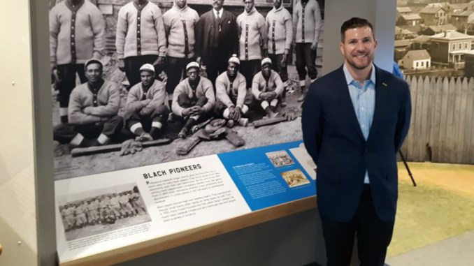 Michael Goldklang standing in front of a museum photo of the St. Paul Colored Gophers team (Photo by: Charles Hallman | MSR News)