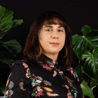 A headshot for Sara Zia Ebrahimi, wearing a black shirt with bright print, and surrounded by plants.
