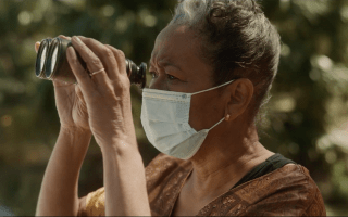 An older Black person with short graying hair, wearing a face mask, looks into a pair of binoculars outside.
