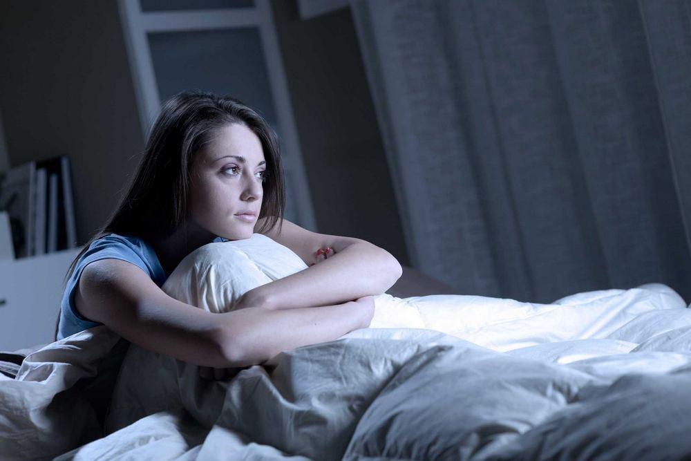 wanita terjaga di tempat tidur karena mengalami insomnia
