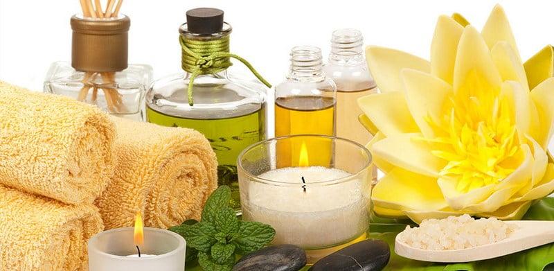 botol berisi minyak atsiri, handuk dan lilin aromaterapi disusun di atas meja