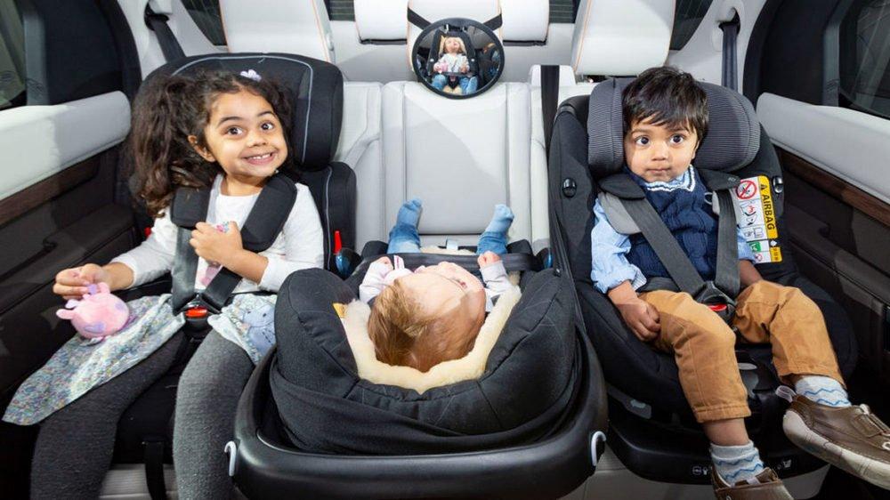 dua orang anak dan satu bayi menggunakan car seat
