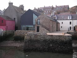Digital photo of the Pier Arts Centre on the shore near the pier, with the rear of building and modern extension with glass, town of Stromness behind