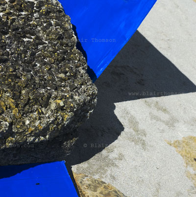 rock texture and moss with angular shapes of blue man made shapes and shadows