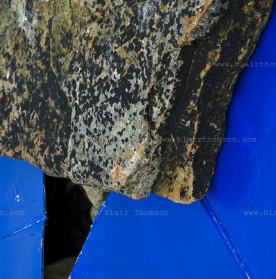 sea rock at top of square with blue shapes underneath and looking through to blackness