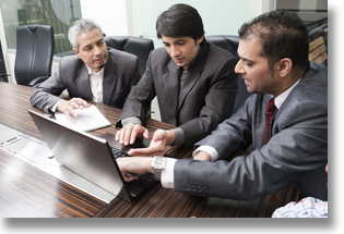 Three businessmen meeting and looking at a laptop screen