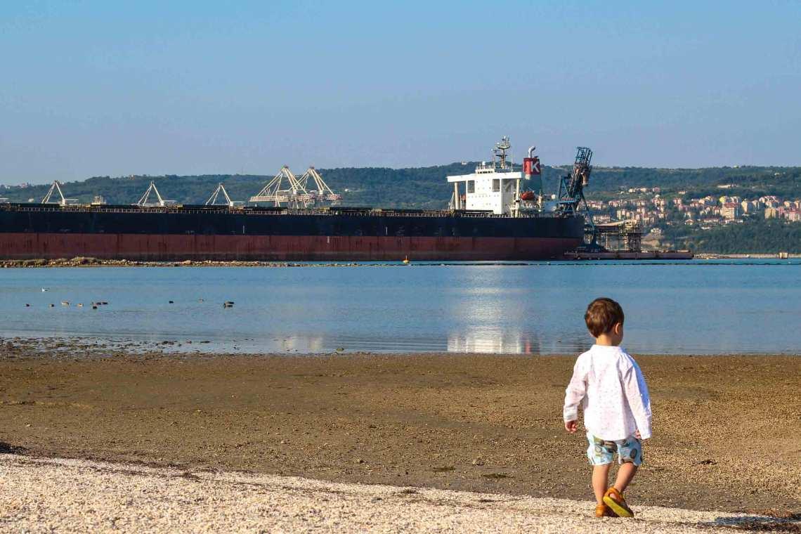Kleinkind schaut auf eine Bucht mit Schiff