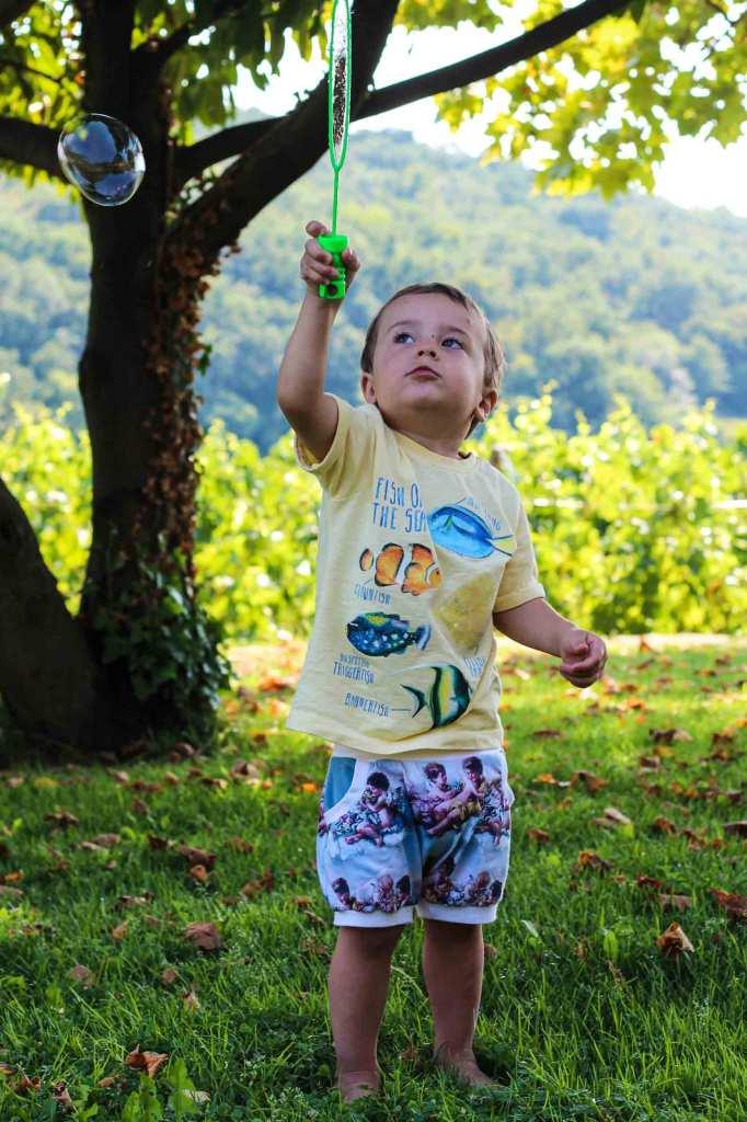Kleinkind am Olivenhain macht Seifenblasen