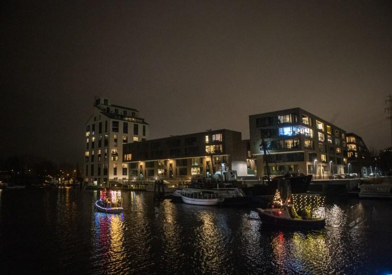Weihnachtlich geschmückte Boote fahren durch den Harburger Binnenhafen