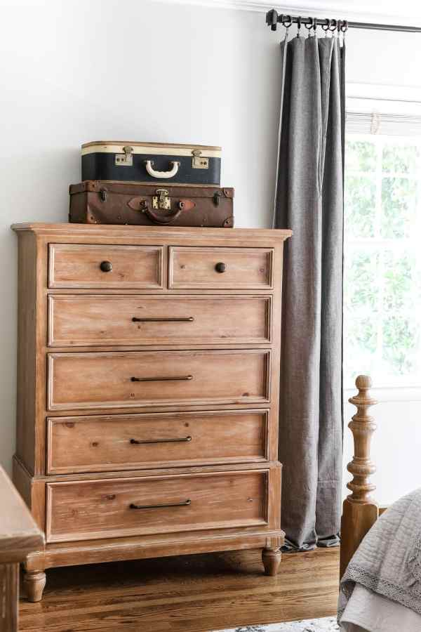 Tried and true ways to decorate and refresh your home completely for free (and maybe even make a little money in the process). #decorating #homedecor #budgetdecor An old suitcase for extra storage on a bedroom dresser