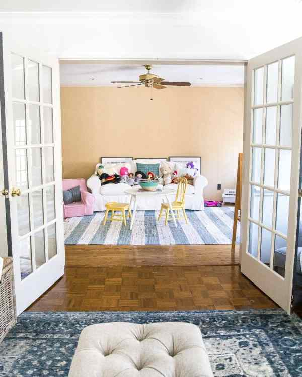 Before of a playroom pre-makeover with French doors | blesserhouse.com - A dated and disorganized playroom gets a fresh, modern, sweet design plan with storage solutions, bright colorful accents, and room to create. #playroom #designboard #moodboard #kidsroom