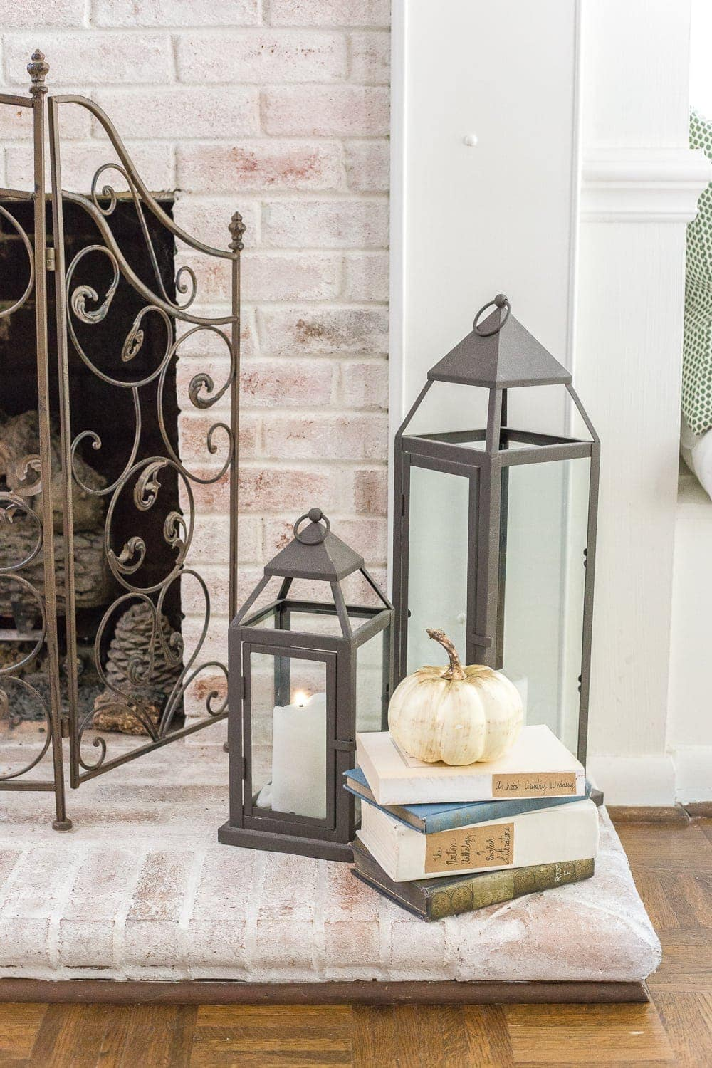 Lanterns and pumpkin on a hearth to add coziness for fall