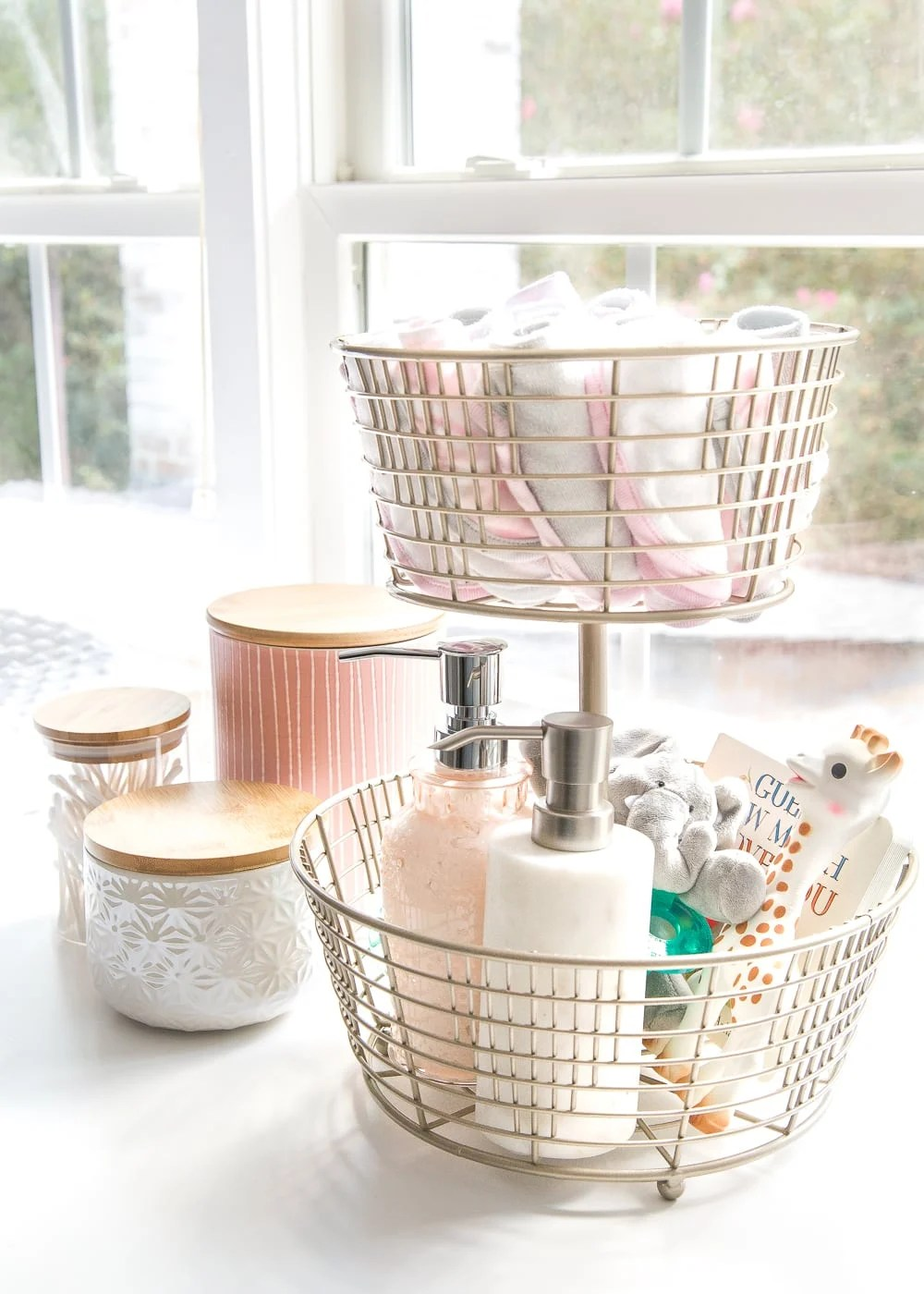 Nursery Organization | Use a tiered fruit basket from the kitchenware aisle to store baby washcloths, grabby toys, Wubbanubs, lotion, and hand sanitizer.