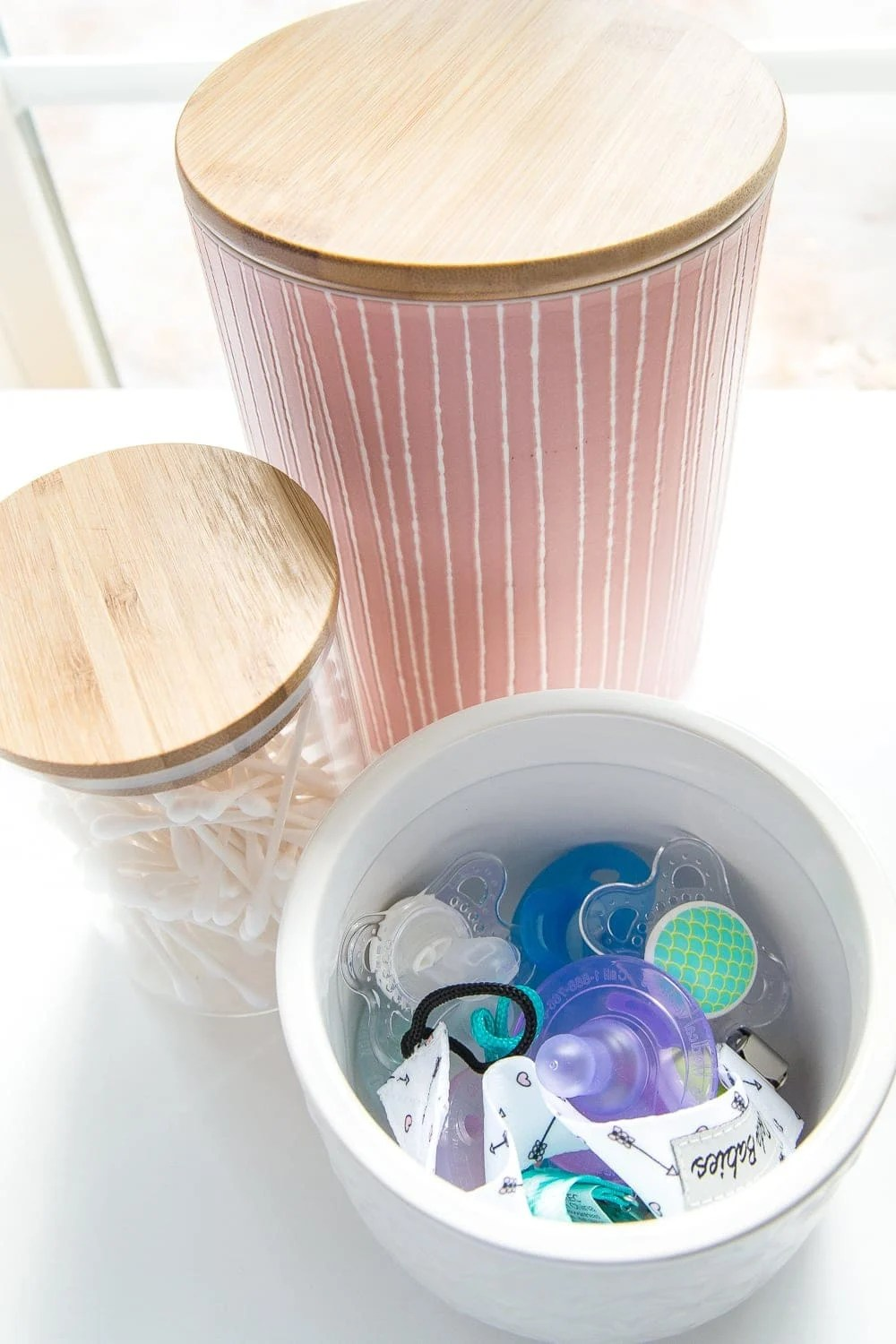 Nursery Organization | Use lidded canisters from the kitchenware aisle to store pacifiers.