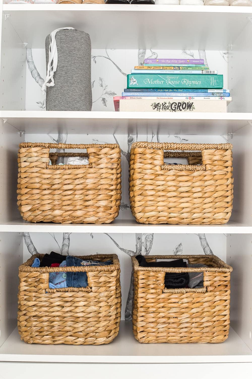 Nursery closet organization with baskets and shelving for books