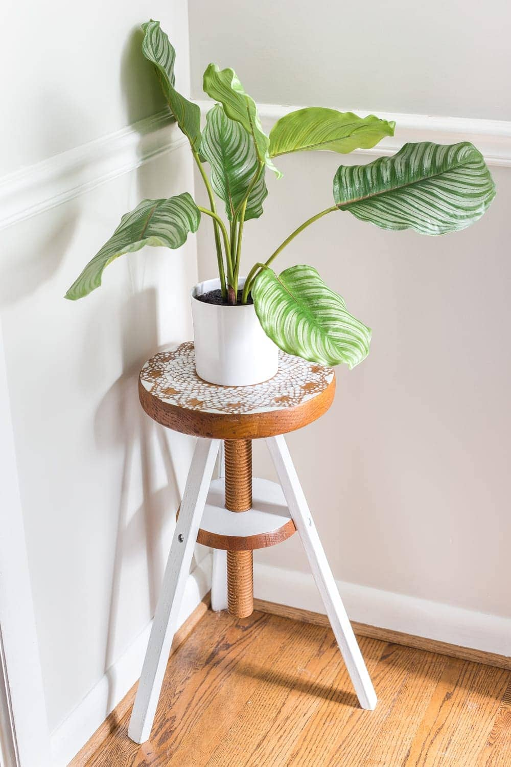 A global designer-inspired DIY plant stand made from a thrifted piano stool using just spray paint and a doily for a quick and easy makeover. #plantstand #pianostool #globaldecor #spraypaint #thriftstoreflips #thrifting #diyhomedecor #thriftedhomedecor