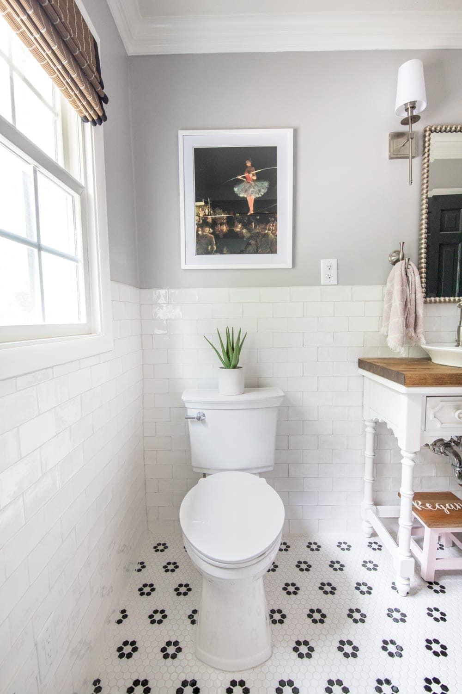 Girls' Bathroom Decor Details & Sources | Self cleaning toilet, retro flower floor tile, handmade subway wall tile, and vintage tightrope walker art