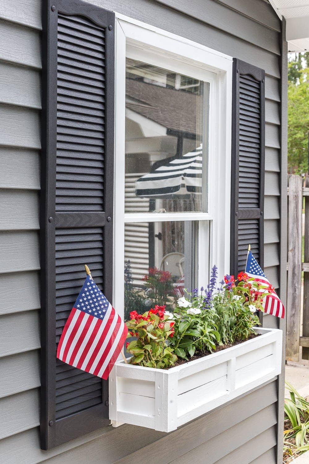 DIY window box using scrap wood with red, white, and blue patriotic flowers for July 4th