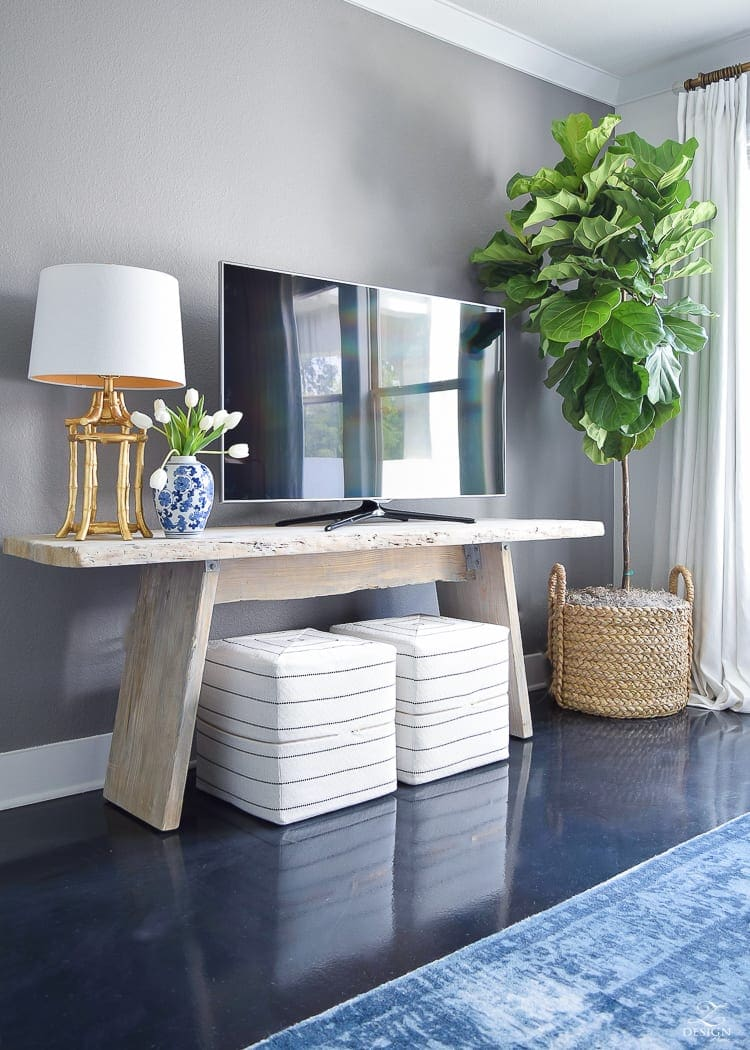 Add visual height beside a TV to distract from it. Add a floor lamp or a tall plant and suddenly that TV doesn't stick out quite so much.