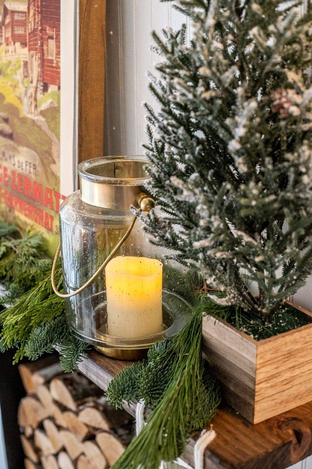 Christmas mantel decor with fresh greenery, mini trees, and glass lanterns