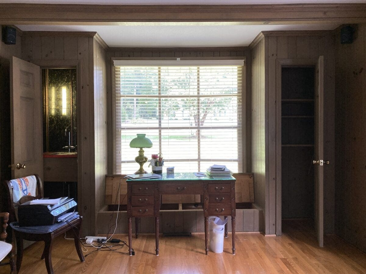 office in living room with wood paneling