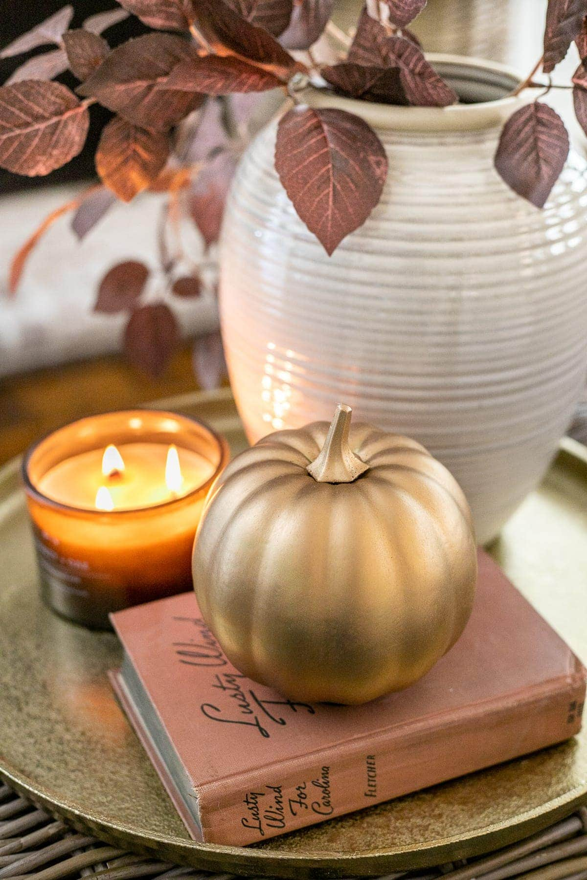 fall decor on a tray with vase of leaves, candle, and pumpkin