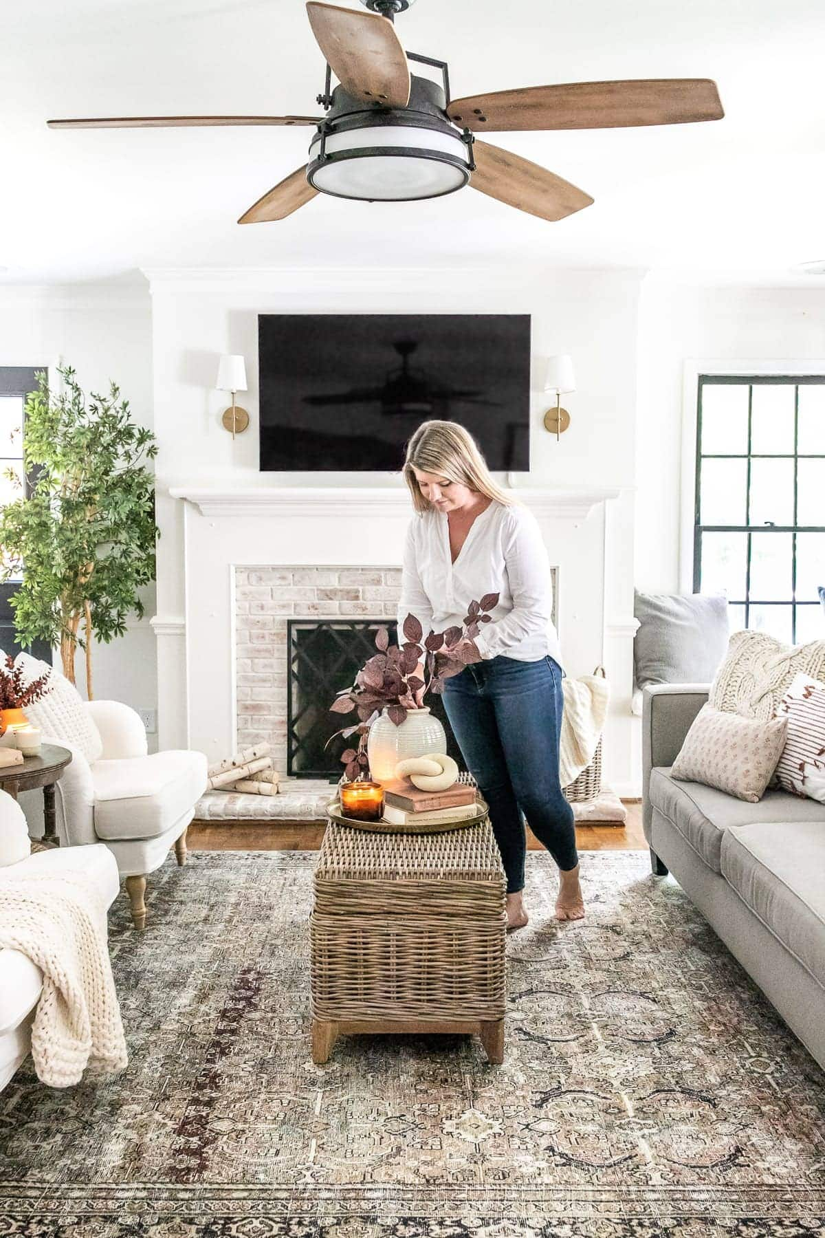 living room decorated for fall with ceiling fan and tv above fireplace