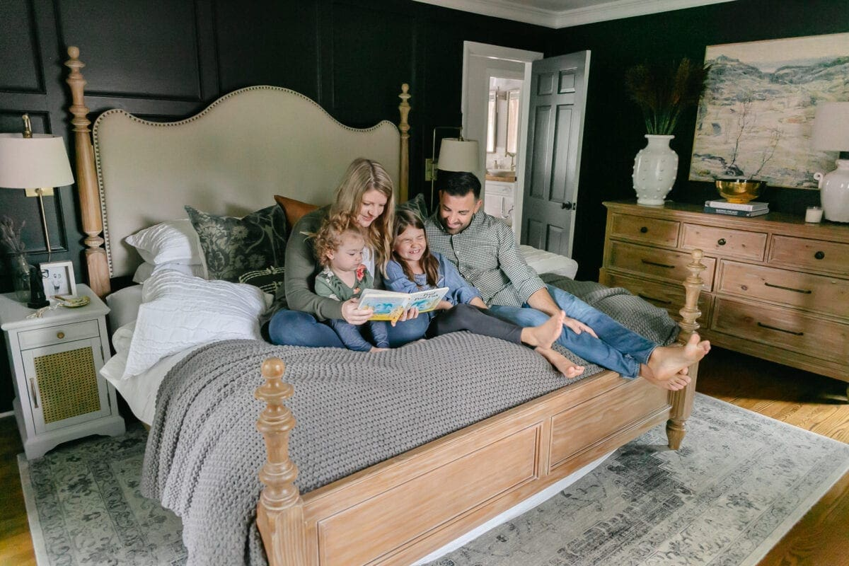 Family reading on a bed with black painted walls and wood furniture