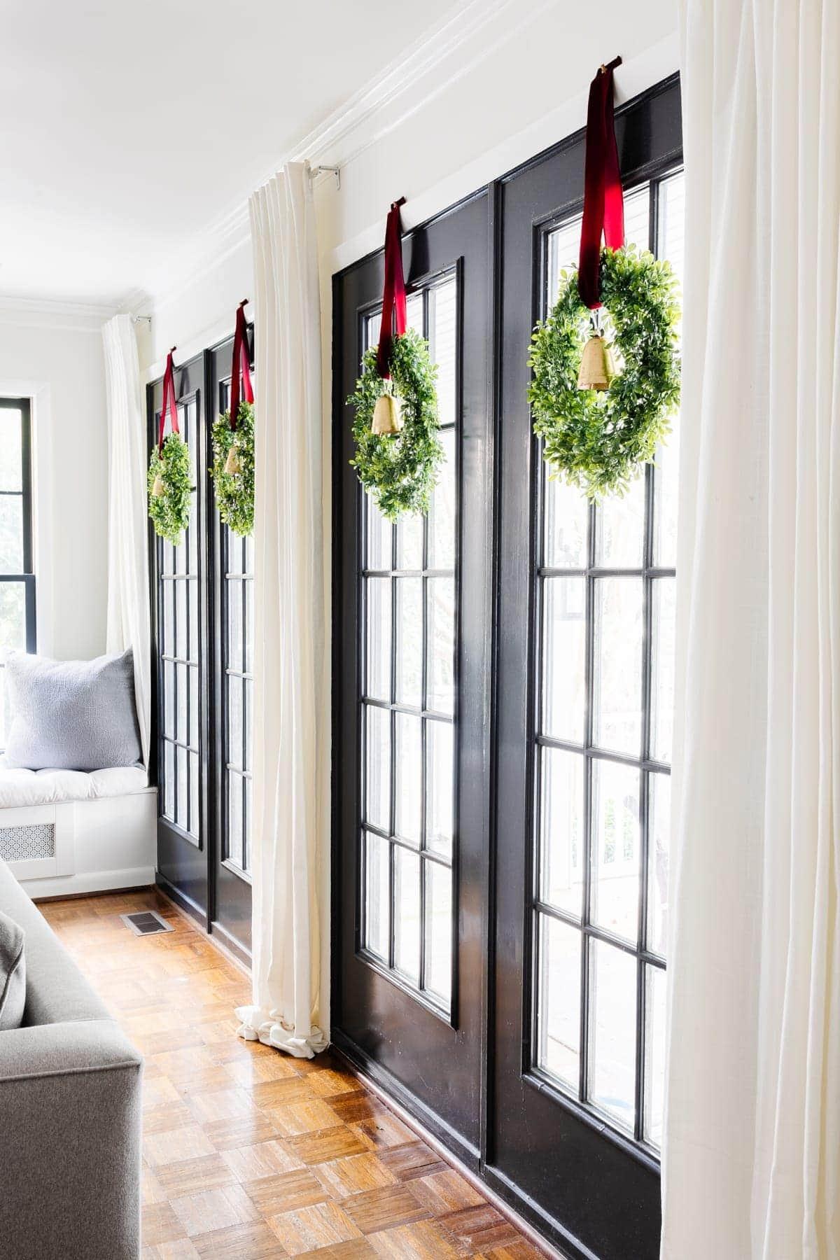 Grandes de Natal penduradas nas janelas das portas francesas