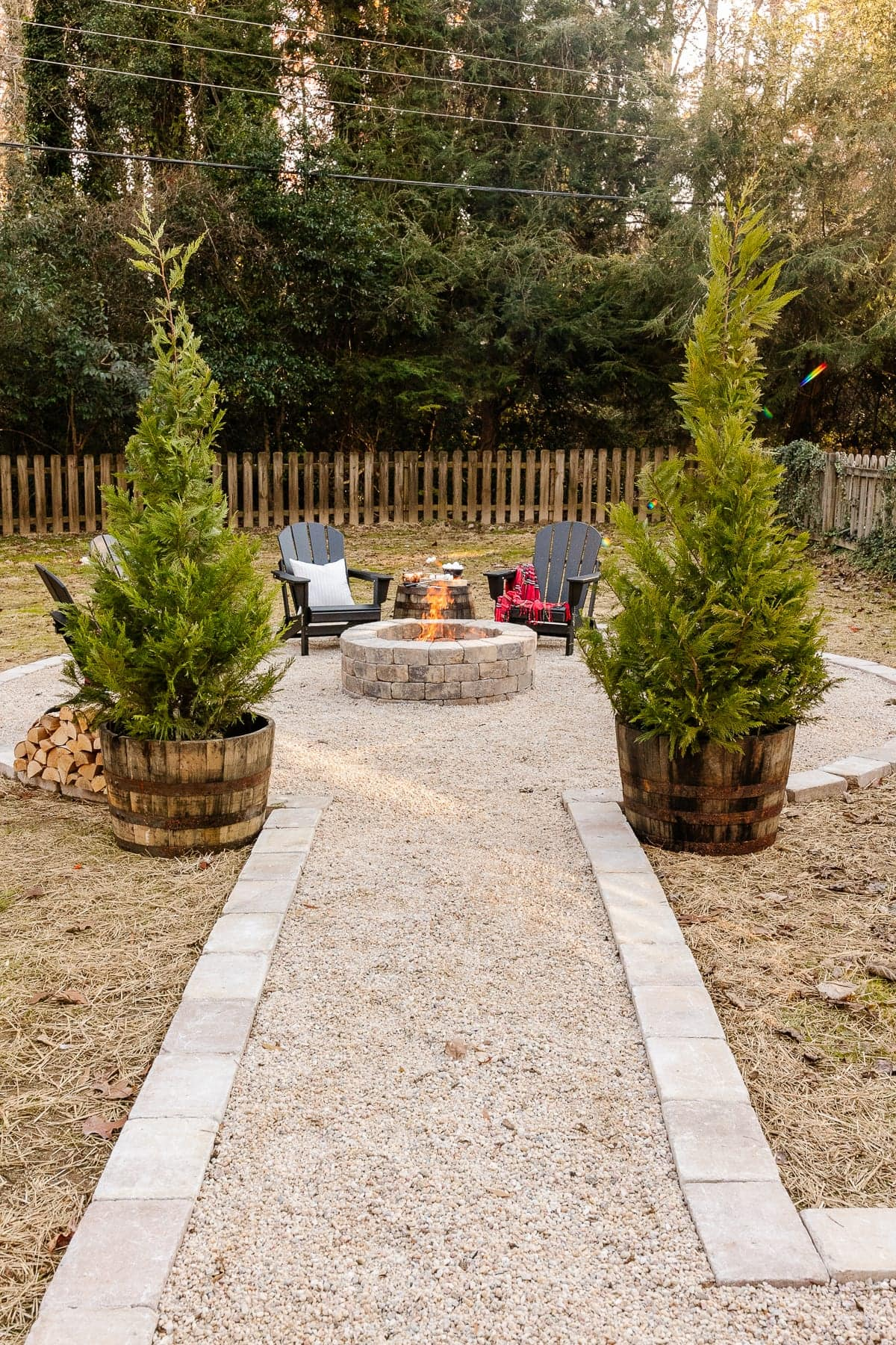Fire pit with pea gravel, stone edge, and adirondack chairs