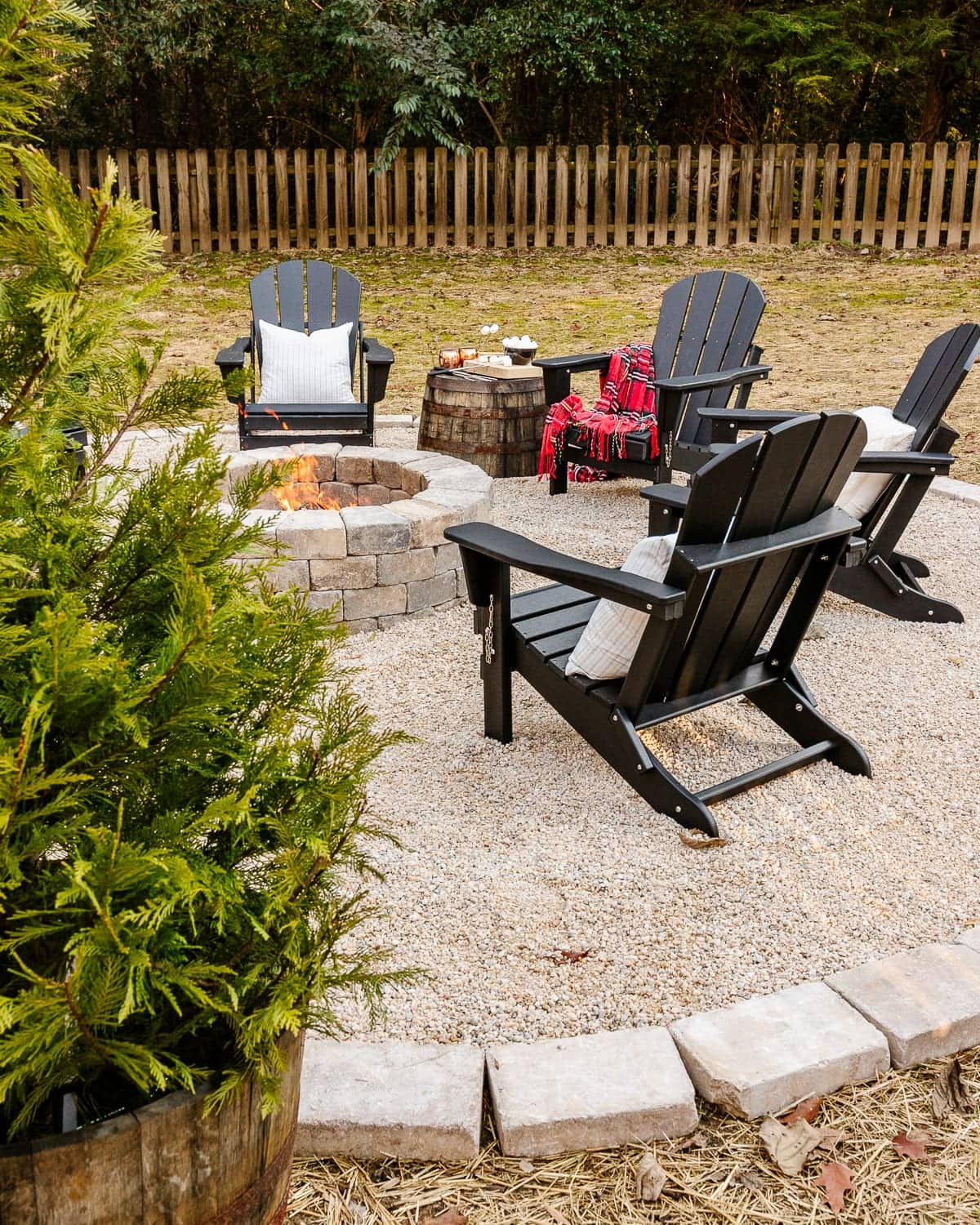 Stone fire pit with pea gravel, stone edgers, and adirondack chairs