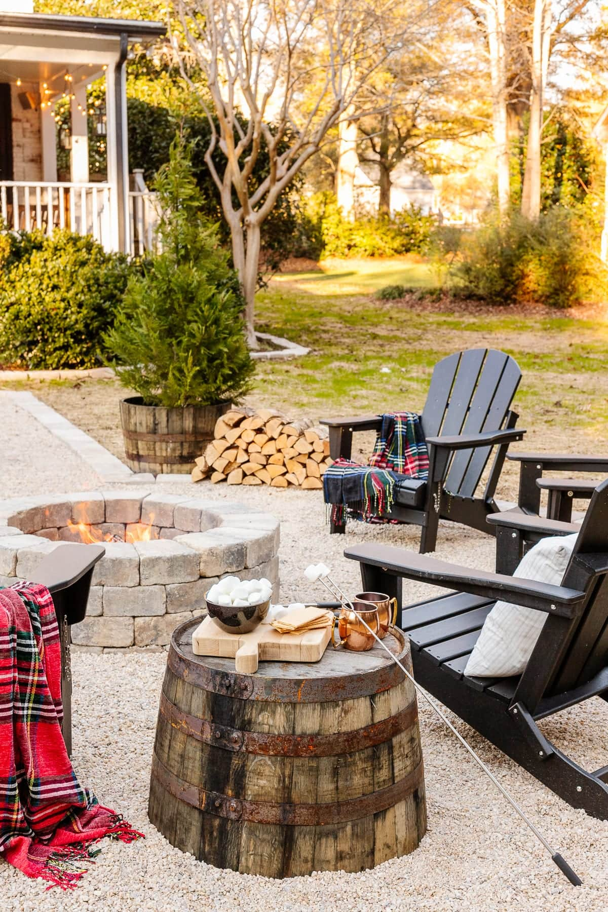 stone fire pit with pea gravel, stone edgers, and adirondack chairs with barrel planter for a side table