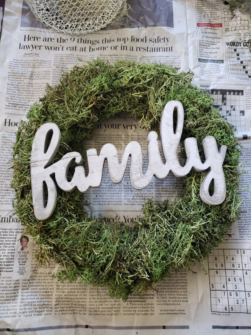 Attach the wood lettering sign to the wreath with hot glue.