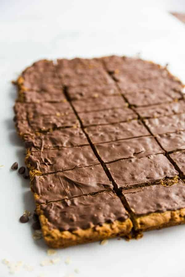 Chocolate Peanut Butter Oatmeal Cookie Bars with a shiny chocolate topping, cut into square, ready to be enjoyed.