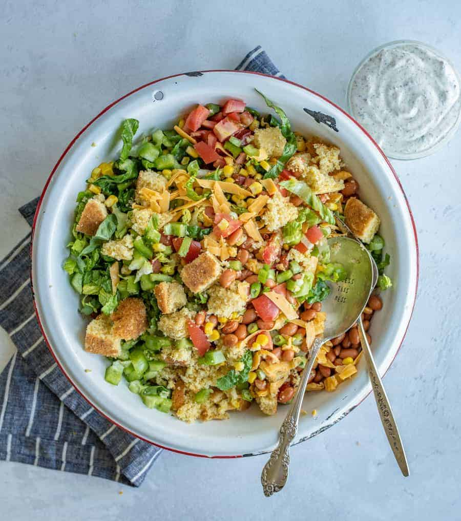 This cornbread salad has all of your favorite summertime flavors, like tomatoes, corn, pinto beans, and the star of the show, cornbread, and it's topped with a rich and creamy homemade ranch dressing! It's a perfect party dish.