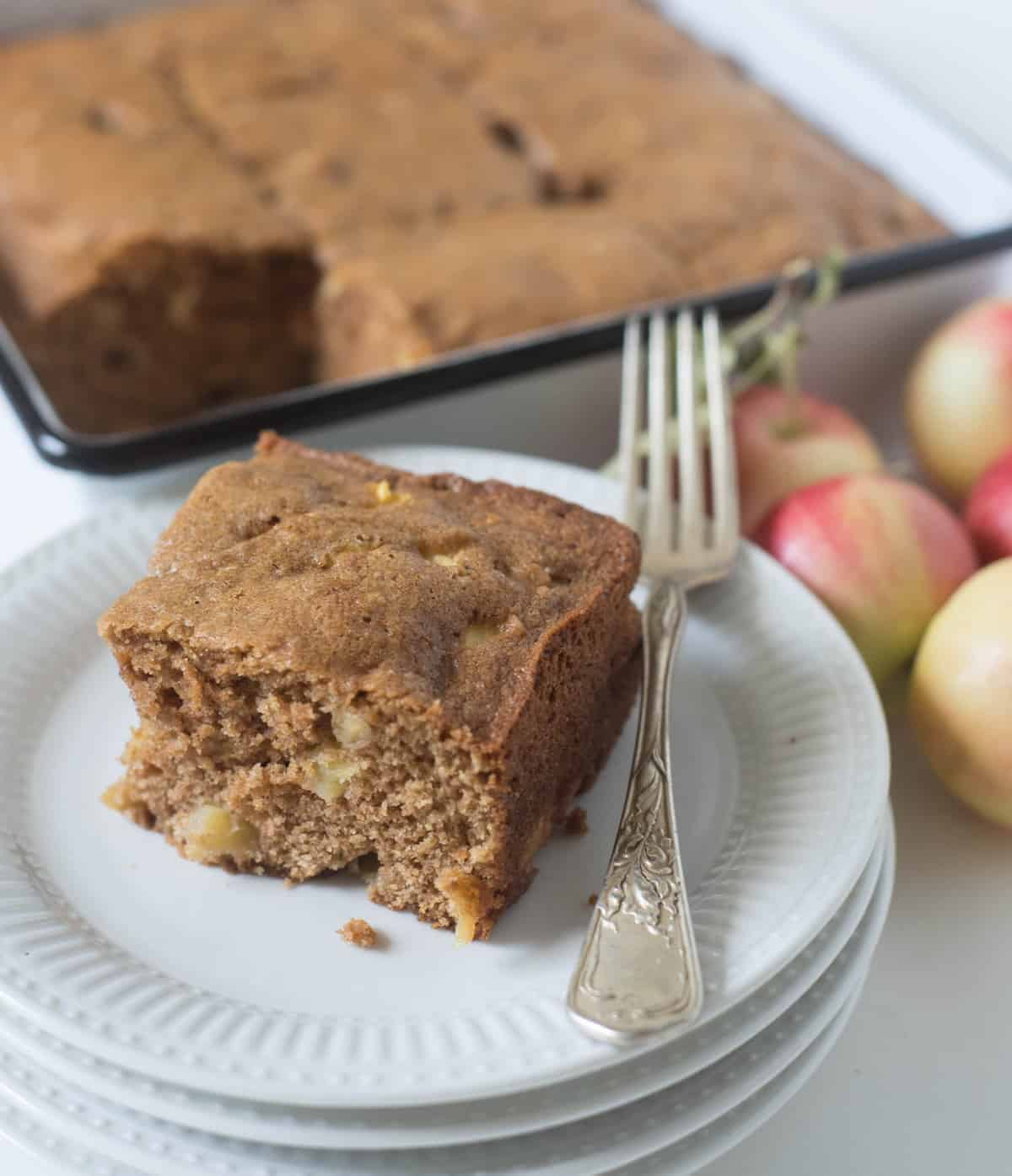 A plate with a square piece of easy apple cake and a fork