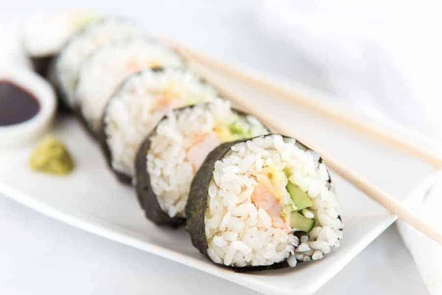 easy shrimp sushi roll on white dish with chopsticks