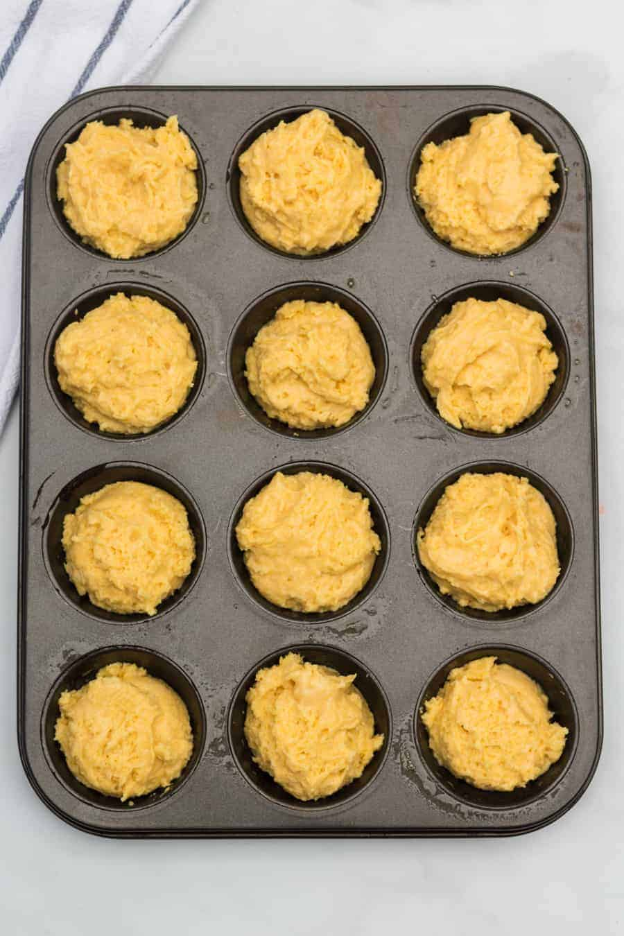 Corn muffin batter in a muffin pan waiting to go into the oven.