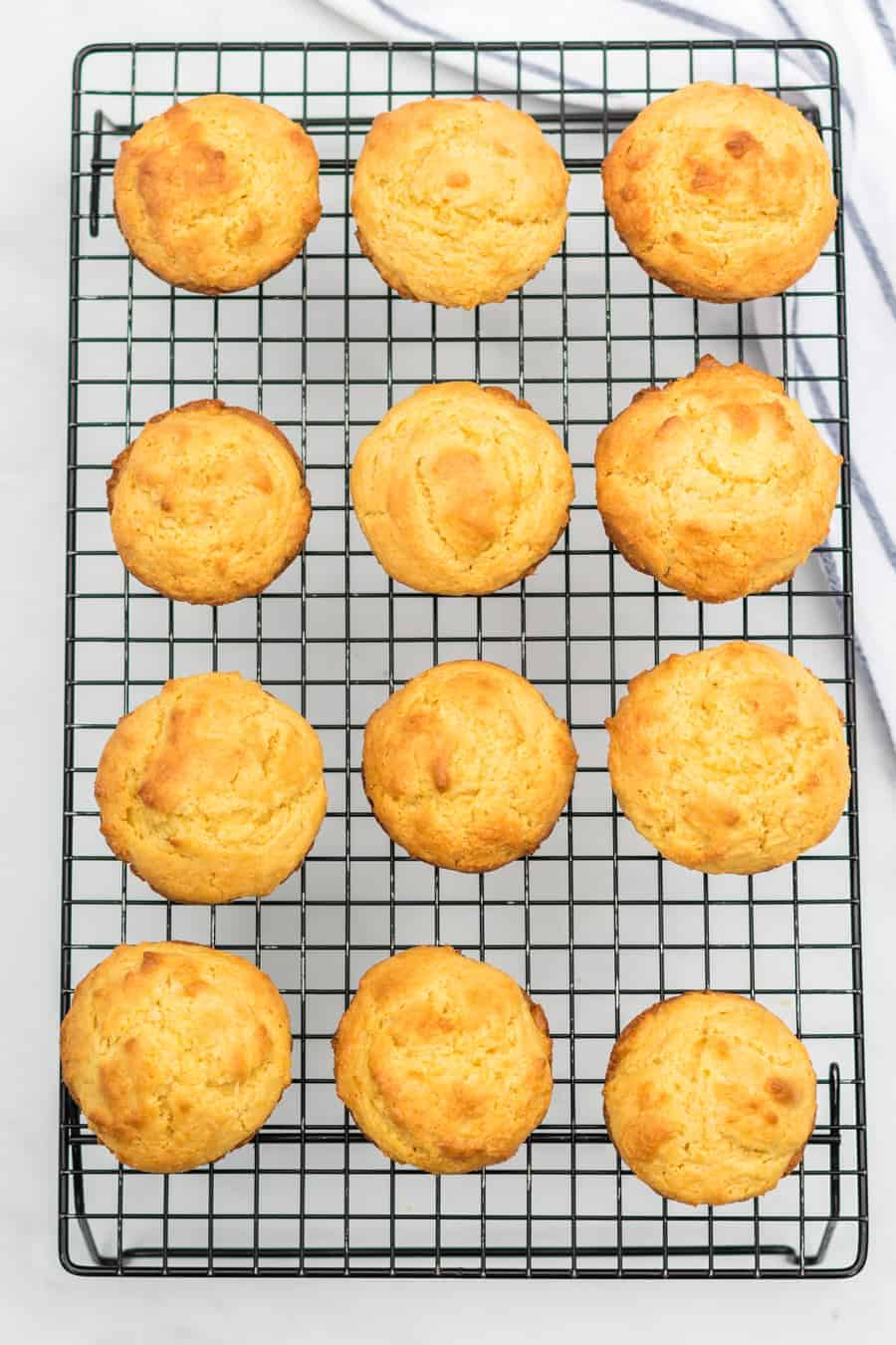 12 baked and golden corn muffins rest on a wire cooling rack.