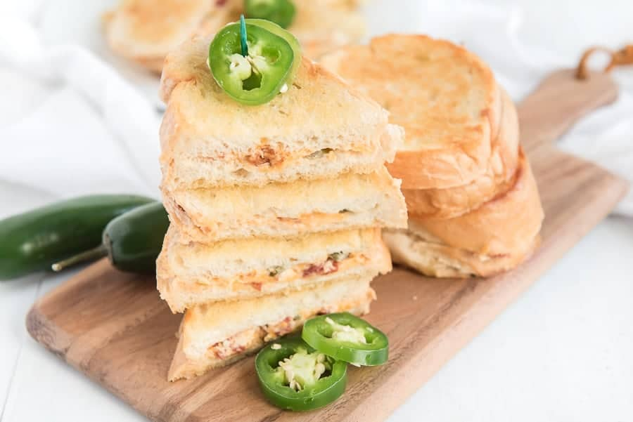 jalapeno grilled cheese on white plate with jalapenos on toothpick and a side of potato chips