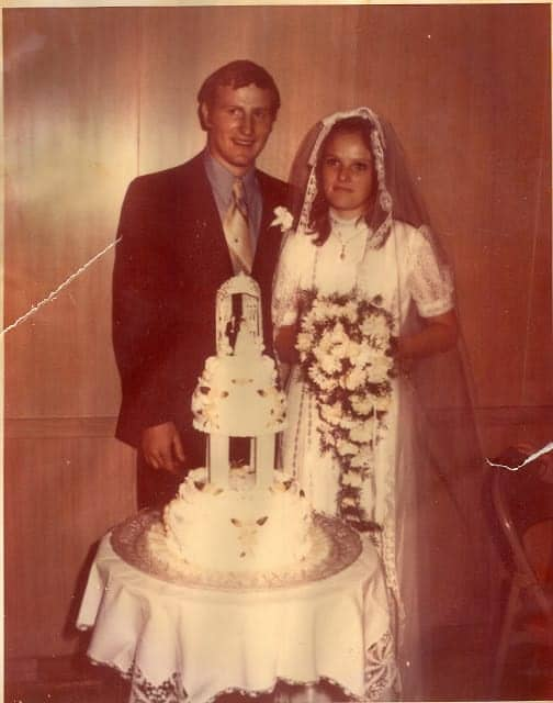 An old wedding photo of a couple with their wedding cake