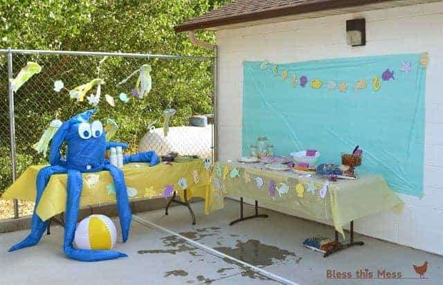 Two party tables with a giant inflatable octopus and beach-themed decorations