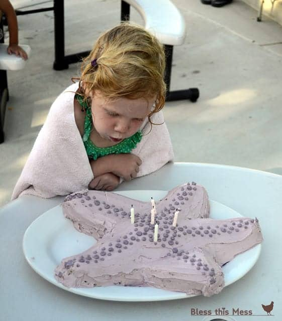 A girl in a bathing suit and towel blowing out candles on a starfish shaped birthday cake