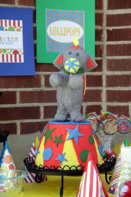 An elephant birthday cake surrounded by a table of circus-themed decorations