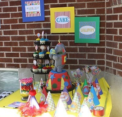 An elephant birthday cake on a table with circus-themed decorations, party hats, cupcakes in front of a brick wall with circus-themed signs