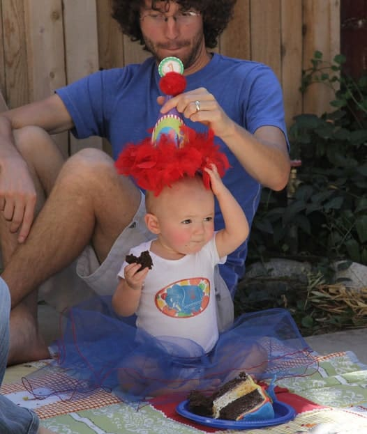 A baby wearing a blue tutu and circus-themed shirt and party hat sitting on the ground eating birthday cake