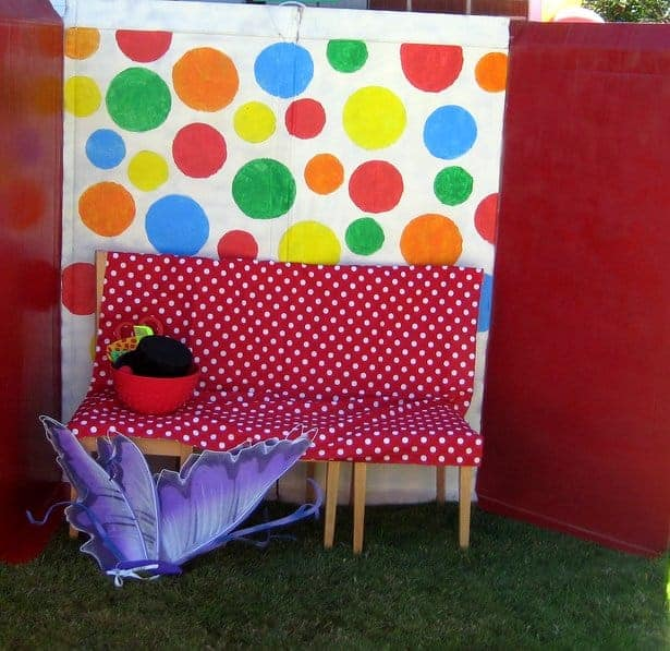 A circus-themed outdoor photo booth with polka-dot background, bench and props